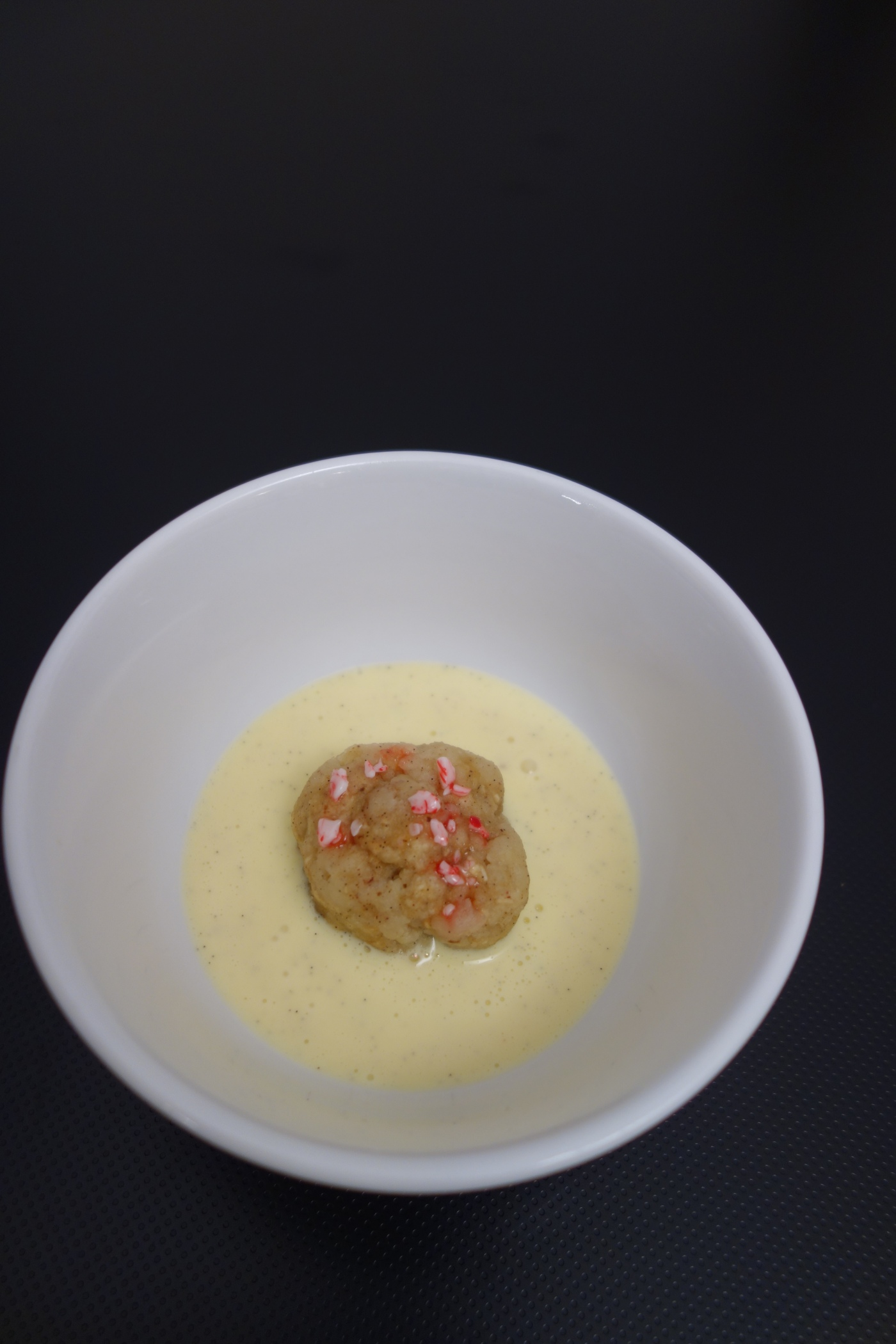 "Sweet matzo ball in creme anglaise ""soup""  topped with crushed candy cane"